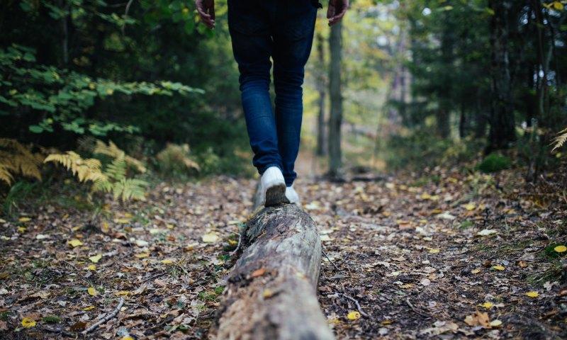 Someone balancing on a log.