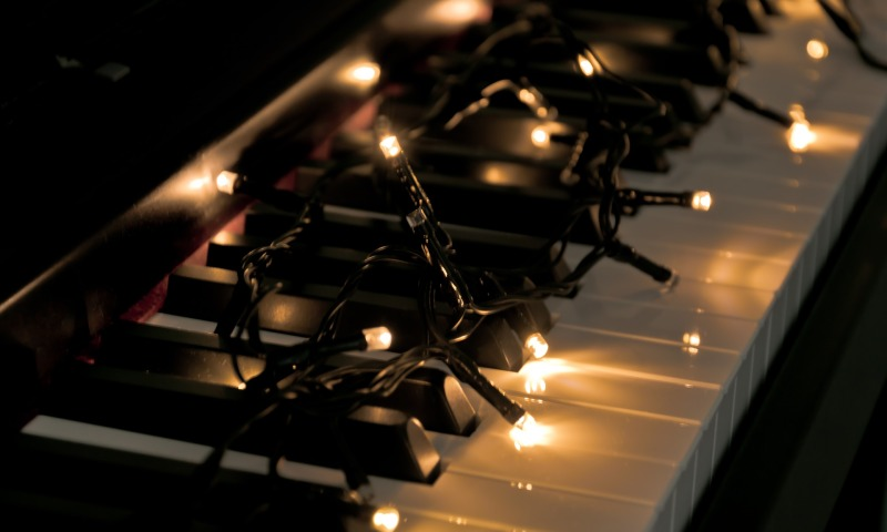 Close up of piano keys with fairy lights