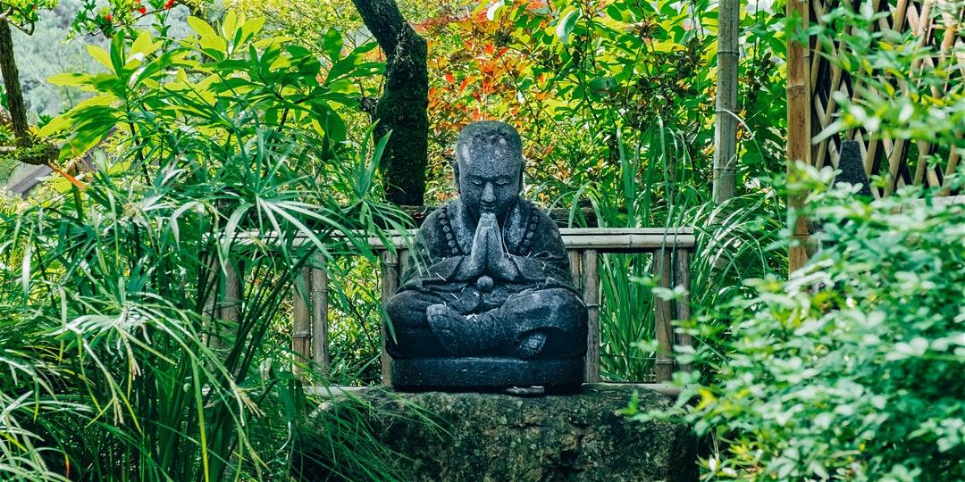 Buddha statue in lush green garden.